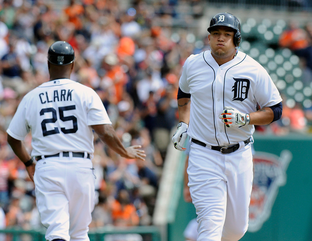 . Detroit Tigers\' Miguel Cabrera, right, runs past third base coach Dave Clark towards home plate after hitting a two-run home run in the first inning against the San Francisco Giants in a baseball game Saturday, Sept. 6, 2014, in Detroit, Mich.  AP Photo/Jose Juarez)