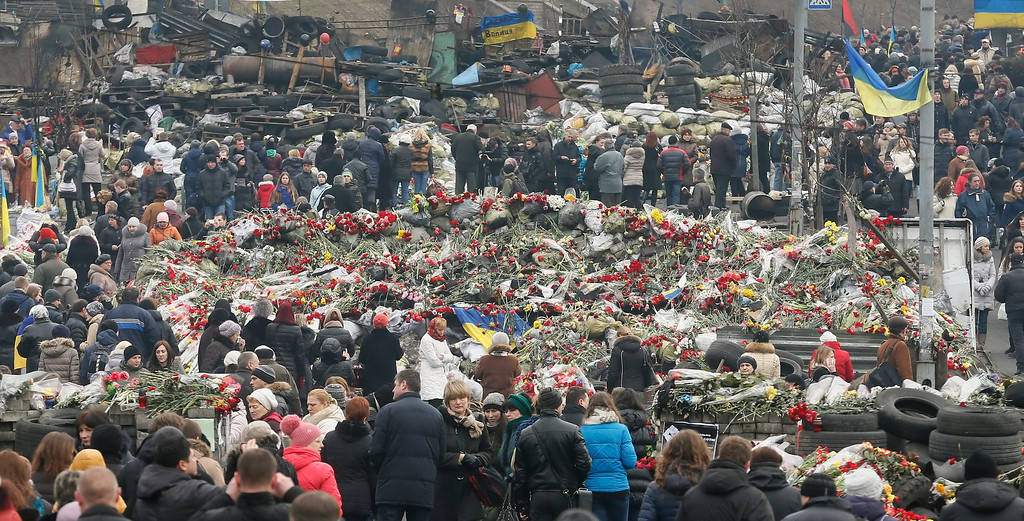 . Ukrainians encircle an area filled with floral ltributes and candles  as they remember those killed during the recent violent protests, in Kiev, Ukraine, 26 February 2014.  Former Ukrainian president Viktor Yanukovych had his first public appearance  in Rostov, Russia, since being ousted. He told the there he would fight for his country and insisted he was not overthrown.  EPA/SERGEY DOLZHENKO