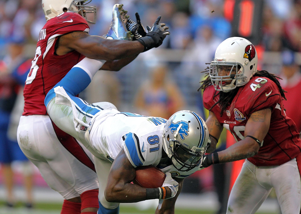 . Detroit Lions wide receiver Calvin Johnson (81) is tackled by Arizona Cardinals strong safety Rashad Johnson (49) and Daryl Washington during the first half of an NFL football game on Sunday, Dec. 16, 2012, in Glendale, Ariz. (AP Photo/Paul Connors)