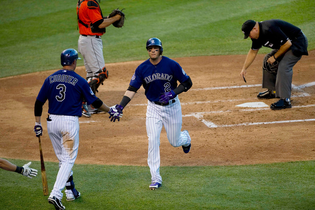 . Troy Tulowitzki #2 of the Colorado Rockies high fives Michael Cuddyer #3 after hitting a home run during the fourth inning of a Major League Baseball game against the Miami Marlins on July 22, 2013 at Coors Field in Denver. (Photo By Grant Hindsley/The Denver Post)