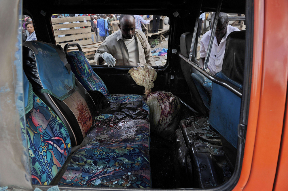 . Police investigators look into a damaged public transport vehicle at the scene of an explosion on May 16, 2014 on the outskirts of Nairobi\'s business district where twin explosions claimed at least 10 lives. Ten people were killed and over 70 wounded in two bomb attacks in a busy market area in the Kenyan capital of Nairobi, officials said Friday. (TONY KARUMBA/AFP/Getty Images)