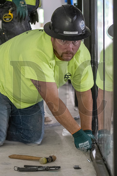 Michael Dowell, a journeyman glazier with Local 740 and an employee of Culver Glass, places an exterior panel on a section of interior storefront in the Wells Fargo Center. (Josh Kulla/DJC)