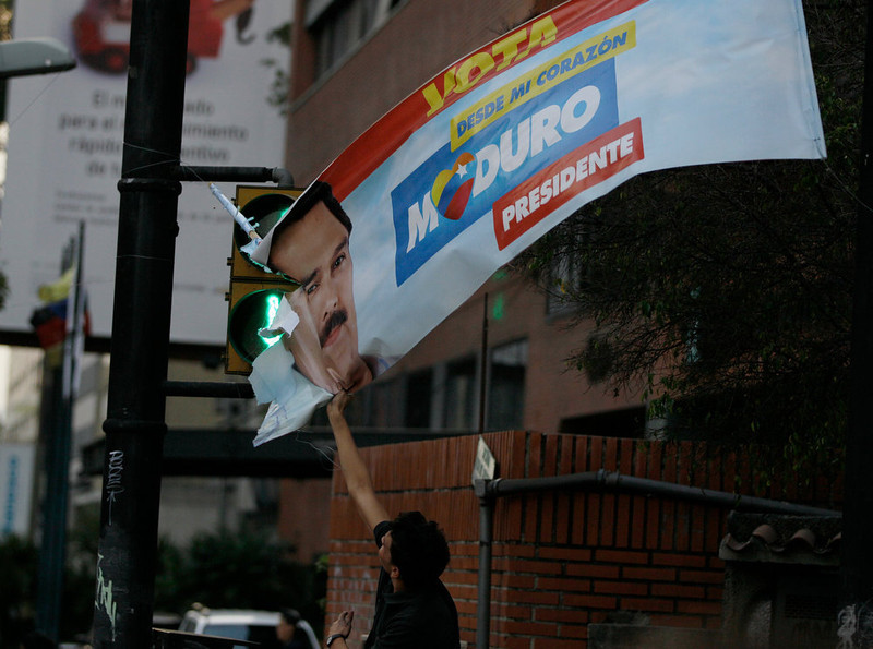 . An opposition supporter pulls down a poster of interim President Nicolas Maduro during protests against the election results in Caracas, Venezuela, Monday, April 15, 2013. National Guard troops dispersed students protesting the official results of Venezuela\'s disputed presidential election. Opposition candidate Henrique Capriles has challenged his narrow loss to Nicolas Maduro and is demanding a recount.  (AP Photo/Fernando Llano)