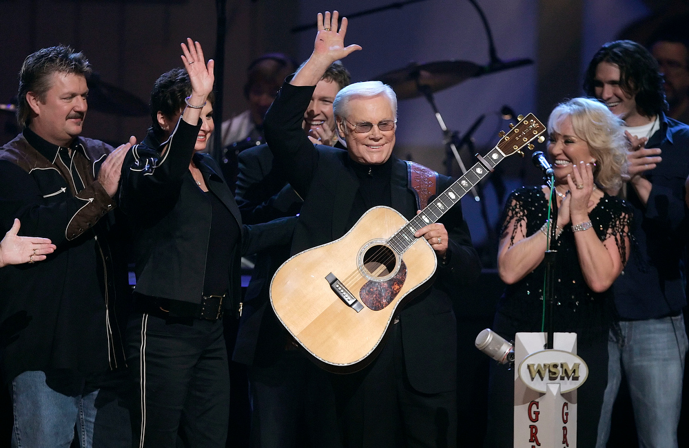 ". FILE - In this Sept. 12, 2006 file photo, Country music legend George Jones waves to the crowd during his 75th birthday celebration at the Grand Ole Opry House in Nashville, Tenn., on Tuesday, Sept. 12, 2006. From left are Joe Diffie; Jones\' wife, Nancy; Craig Morgan; Jones; Tanya Tucker; and Joe Nichols.   Jones, the peerless, hard-living country singer who recorded dozens of hits about good times and regrets and peaked with the heartbreaking classic ""He Stopped Loving Her Today,\"" has died. He was 81. Jones died Friday, April 26, 2013 at Vanderbilt University Medical Center in Nashville after being hospitalized with fever and irregular blood pressure, according to his publicist Kirt Webster.(AP Photo/Mark Humphrey, file)"