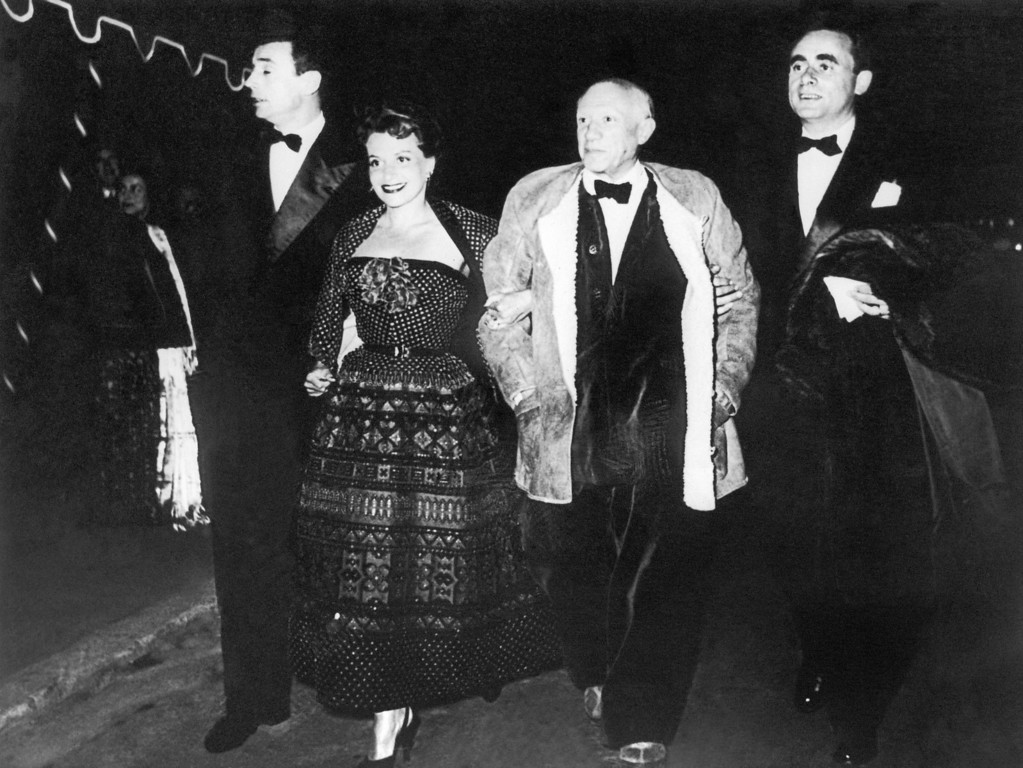 """. Wearing a fur-lined leather jacket over a velvet suit and with a bow tie, Spanish artist Pablo Picasso, strolls arms in arm with Vera Clouzot, wife of the director of the film \""""Wages of Fear\"""" at the Fifth International Film Festival in Cannes, France on April 15, 1953. Because of his attire, the organizers of the festival were at first reluctant to admit him but on Picasso\'s own insistence they let him in. At left French actor Yves Montand and French film director Georges-Henri Clouzot at right. (AP Photo)"""