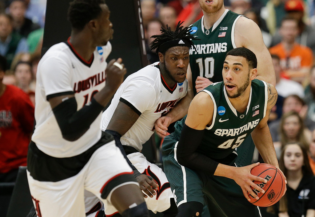 . Louisville\'s Montrezl Harrell, center, defends Michigan State\'s Denzel Valentine (45) during the second half of a regional final in the NCAA men\'s college basketball tournament Sunday, March 29, 2015, in Syracuse, N.Y.  (AP Photo/Seth Wenig)