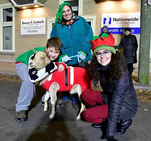 12/7/2018 Mike Orazzi | Staff Bradley Mountain Farm's Josh and Allison Wolfe and Avery Martin with Cinnaman the goat during White Christmas in the Community in downtown Southington Friday evening.