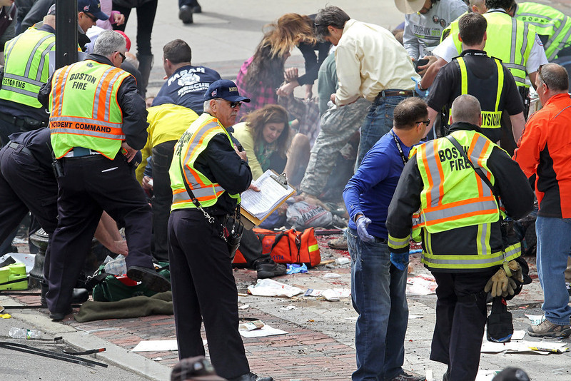 . Rescue personnel aid injured people near the finish line of the 2013 Boston Marathon following explosions in Boston, Monday, April 15, 2013. Two explosions shattered the euphoria of the Boston Marathon finish line on Monday, sending authorities out on the course to carry off the injured while the stragglers were rerouted away from the smoking site of the blasts. (AP Photo/The Boston Herald, Stuart Cahill)