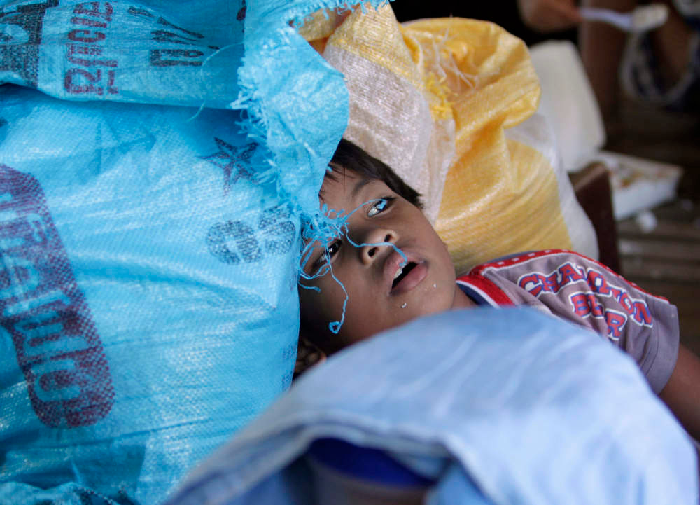 Description of . A boy rests among sacks of rice at an evacuation centre for residents who were rendered homeless after their houses were swept by floodwaters at the height of Typhoon Bopha, in New Bataan town in Compostela Valley, southern Philippines December 8, 2012. Philippine President Benigno Aquino declared a state of national calamity on Saturday, four days after this year\'s strongest typhoon left nearly 1,000 people dead or missing mostly in the country\'s resource-rich south. REUTERS/Erik De Castro