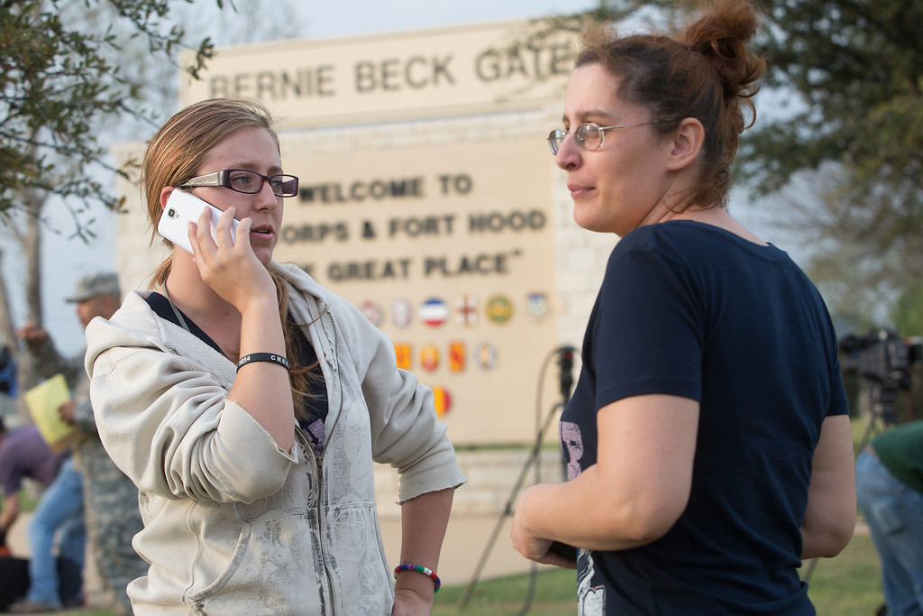 . Krystina Cassidy and Dianna Simpson attempt to make contact with their husbands who are stationed inside Fort Hood, while standing outside of the Bernie Beck Gate, on Wednesday, April 2, 2014, in Fort Hood, Texas. At least one person was killed and 14 injured in a shooting Wednesday at Fort Hood, and officials at the base said the shooter is believed to be dead. (AP Photo/ Tamir Kalifa)