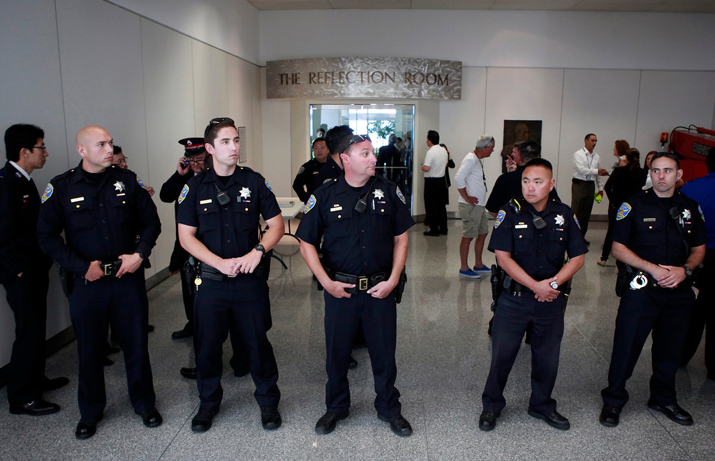 . San Francisco Police stand guard at the Reflection Room at San Francisco International Airport where officials are dealing with family and friends of passengers aboard the Asiana Airlines Flight 214 that crashed during landing Saturday afternoon July 6, 2013.  (Karl Mondon/Bay Area News Group)