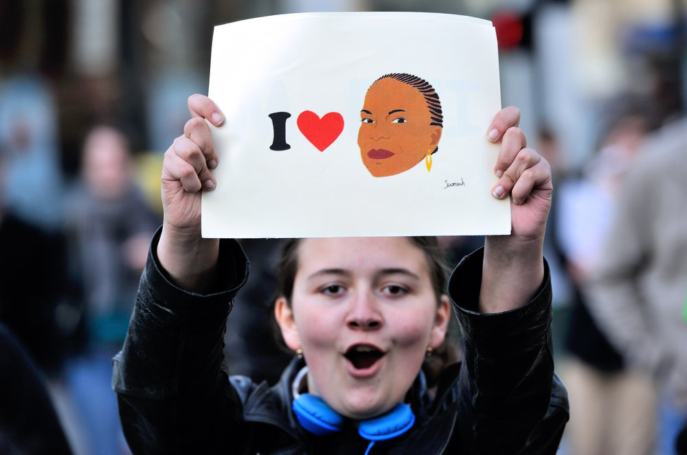 """. A woman holds a board which reads \""""I love you\"""" with the drawing of French Justice Minister Christiane Taubira as she celebrates the newly adopted same sex marriage law, on April 23, 2013 in Lille, northern France. After months of acrimonious debate and hundreds of protests that have occasionally spilled over into violence, the assembly adopted the bill legalizing same-sex marriages and adoptions for gay couples. In its second and final reading, a majority of lawmakers approved the bill by a vote of 331 to 225. Taubira was the main government  member to present and debate with the opposition on the bill at the National Assembly.   PHILIPPE HUGUEN/AFP/Getty Images"""