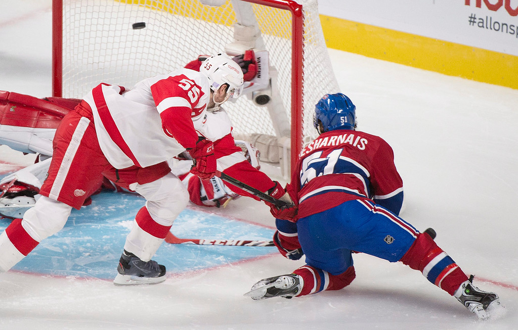 . Montreal Canadiens\' David Desharnais (51) scores against Detroit Red Wings goaltender Jimmy Howard, left, as Red Wings\' Niklas Kronwall (55) defends during overtime period NHL hockey action in Montreal, Tuesday, Oct. 21, 2014. (AP Photo/The Canadian Press, Graham Hughes)
