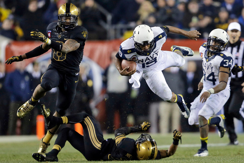 . Navy\'s Keenan Reynolds (19) is tackled by Army\'s Josh Jackson, bottom, as Army\'s Geoffery Bacon, left, and Navy\'s Noah Copeland (34) look on during the second half of an NCAA college football game Saturday, Dec. 8, 2012, in Philadelphia. Navy won 17-13. (AP Photo/Matt Rourke)