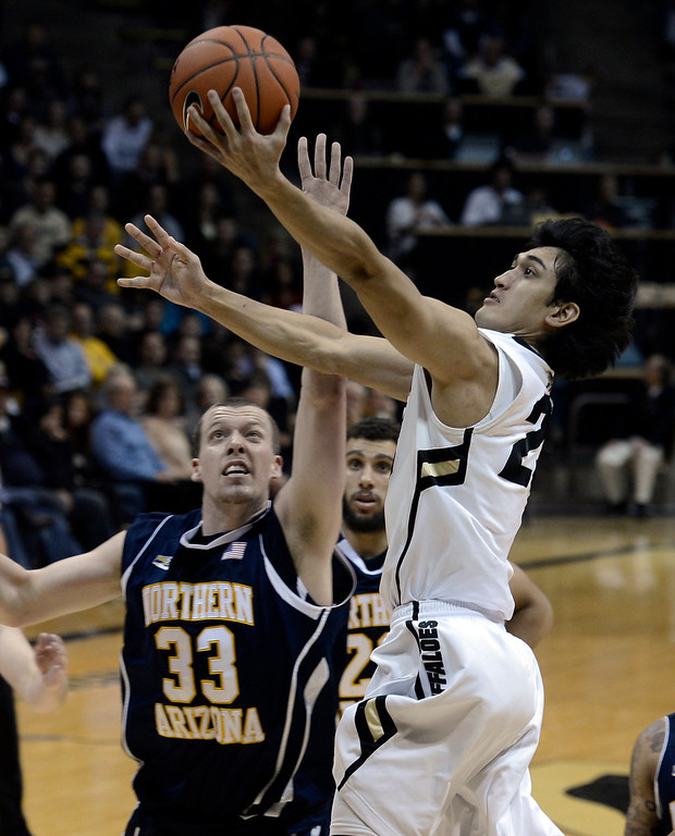 . University of Colorado\'s Sabatino Chen goes for a layup over Max Jacobsen during a game against Northern Arizona on Friday, Dec. 21, at the Coors Event Center on the CU campus in Boulder.    (Jeremy Papasso/Daily Camera)