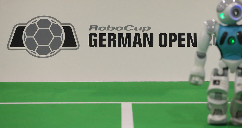 ". A robot stands next to the logo of the ""RoboCup German Open 2014\"" in Magdeburg, eastern Germany on April 3, 2014. 950 participants from 12 countries participate in the three-day tournament. The robots are required to master a variety of disciplines, including communication, soccer, rescue and dance.  AFP PHOTO / DPA/ JENS WOLF /AFP/Getty Images"