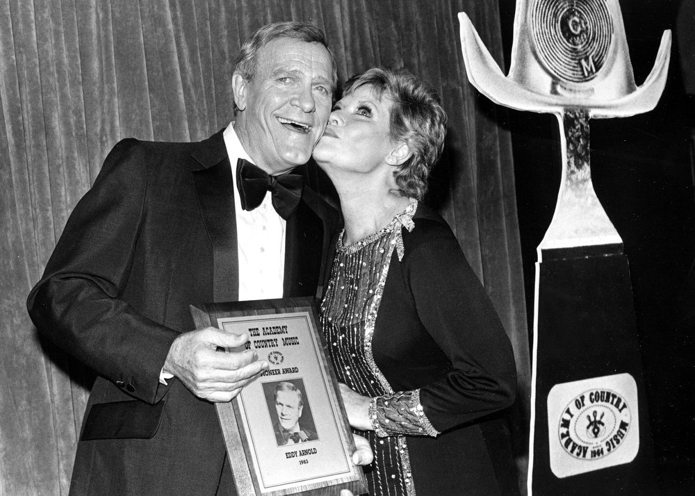. Country Music star Eddy Arnold is kissed by singer Patti Page after receiving the Academy of Country Music\'s Pioneer Award at the 19th annual award presentation at Knorr\'s Berry Farm in Buena Park, Calif., on May 15, 1984. (AP Photo/Nick Ut)