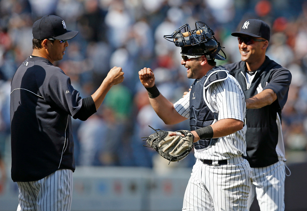 . New York Yankees pitcher Hiroki Kuroda, left, and Derek Jeter, right, celebrate with New York Yankees catcher Francisco Cervelli (29) after the Yankees 1-0 shutout of the Detroit Tigers in a baseball game at Yankee Stadium in New York, Thursday, Aug. 7, 2014.  Neither Kuroda nor Jeter played in the game, watching the action from the dugout. (AP Photo/Kathy Willens)