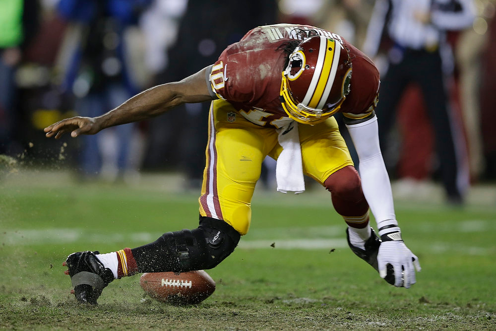 . Washington Redskins quarterback Robert Griffin III twists his knees as he reaches for a loose ball after a low snap during the second half of an NFL wild card playoff football game against the Seattle Seahawks in Landover, Md., Sunday, Jan. 6, 2013. (AP Photo/Matt Slocum)