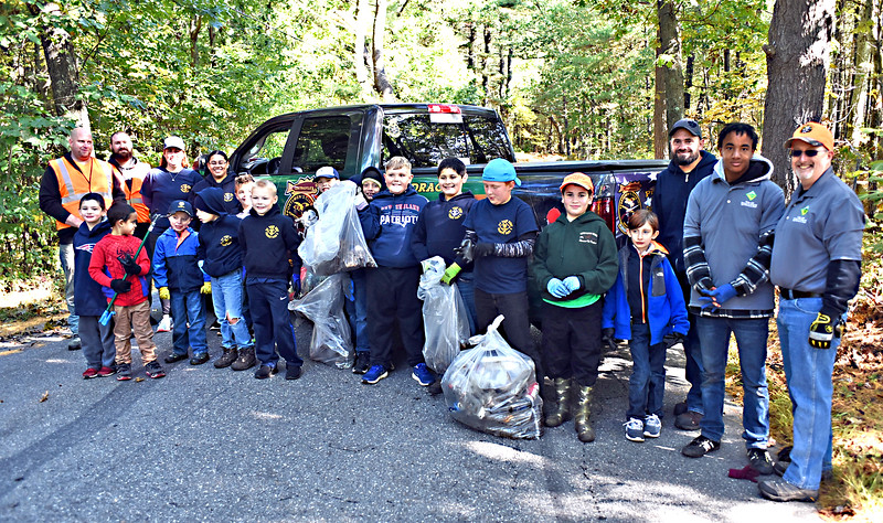 Just a small number of the appox 65 volunteers for the community clean-up along Coburn Road in Dracut led by Josh Taylor (on far left) President of the Centerville Sportsmen's Club, volunteers made up of Cub Scouts from Pack 8 and Boy Scouts from Troop 80 sounts and leaders, both are out of the Centerville Sportsmen Club who organized the event, also help from the Dracut Highway Dept with dumptrucks and a front end loader. SUN/David H.Brow