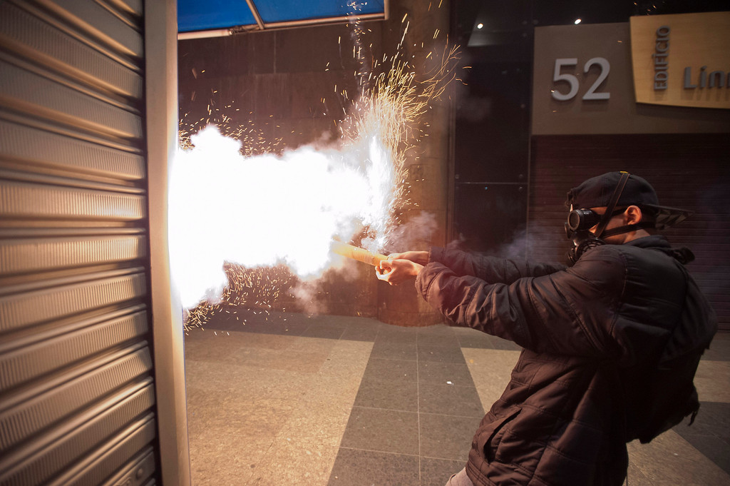 . A masked demonstrator shoots a firework at police during a strike in Rio de Janeiro, Brazil, Thursday, July 11, 2013. Workers across Brazil walked off their jobs in a nationwide strike demanding better working conditions and improved public services in Latin America\'s biggest nation. (AP Photo/Nicolas Tanner)