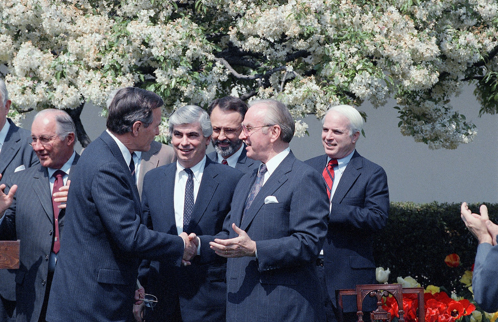 . President George H.W. Bush shakes hands with House Speaker Jim Wright, D-Texas, during a White House Rose Garden Ceremony in Washington, on Tuesday, April 19, 1989 where Bush signed the Central American Bipartisan accord.    Looking on at center are Sen. Christopher Dodd, D-Conn., and Rep. David Bonner, D-Mich. (AP Photo/Charles Tasnadi)