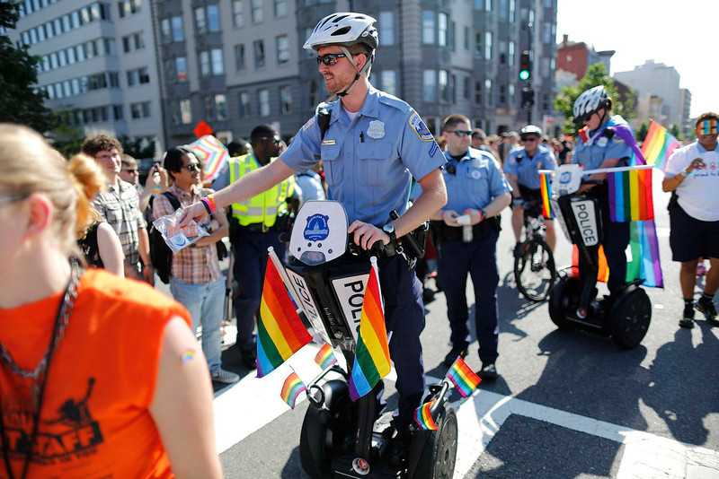 . Washington police officers give out condoms to people in the crowd as they help lead the gay-pride themed Capital Pride Parade in Washington, June 8, 2013. REUTERS/Jonathan Ernst