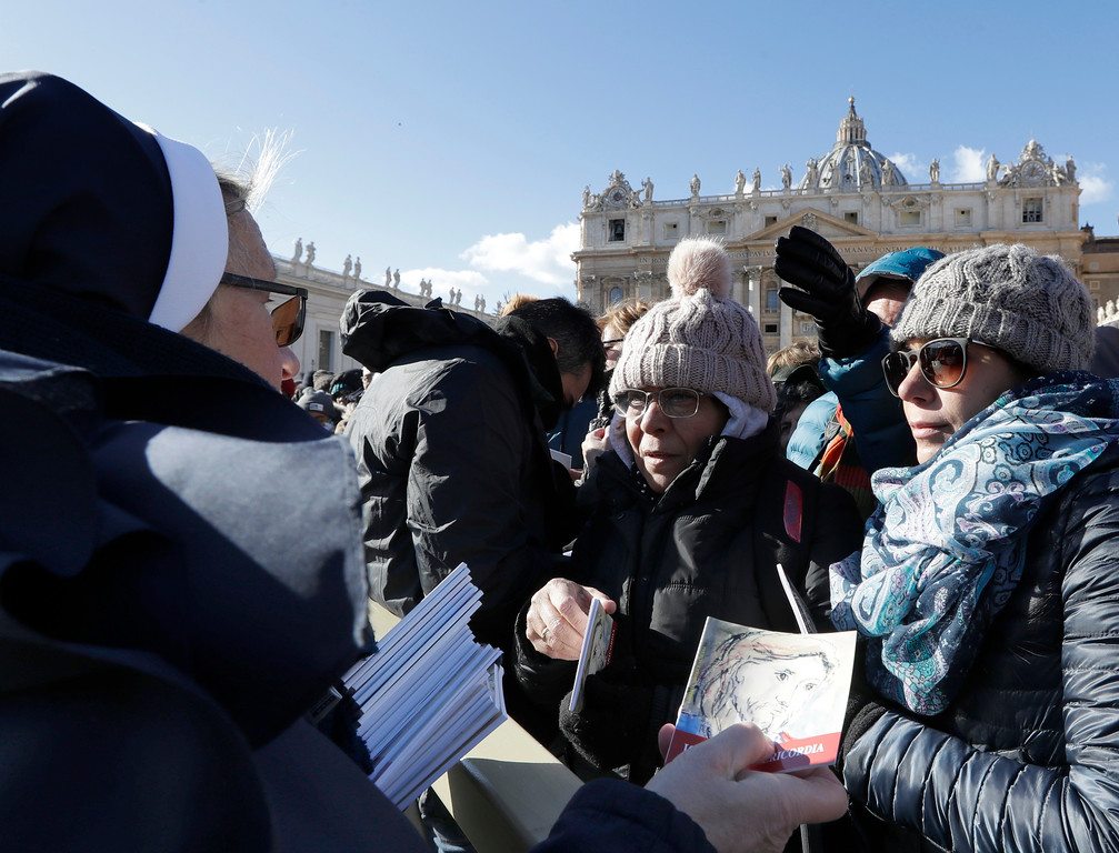 . A nun distributes a booklet after an Epiphany Mass, in St. Peter\'s square at the Vatican, Friday, Jan. 6, 2017.  Homeless people and refugees joined volunteers to hand out 50,000 booklets with biblical tales of God\'s mercy to pilgrims gathered in a frigid St. Peter\'s Square. (AP Photo/Andrew Medichini)