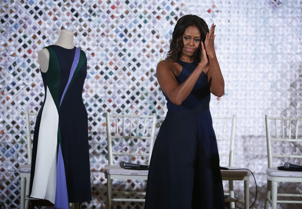 . U.S. first lady Michelle Obama applauds during a session of a Fashion Education Workshop in the East Room of the White House October 8, 2014 in Washington, DC.  (Photo by Alex Wong/Getty Images)