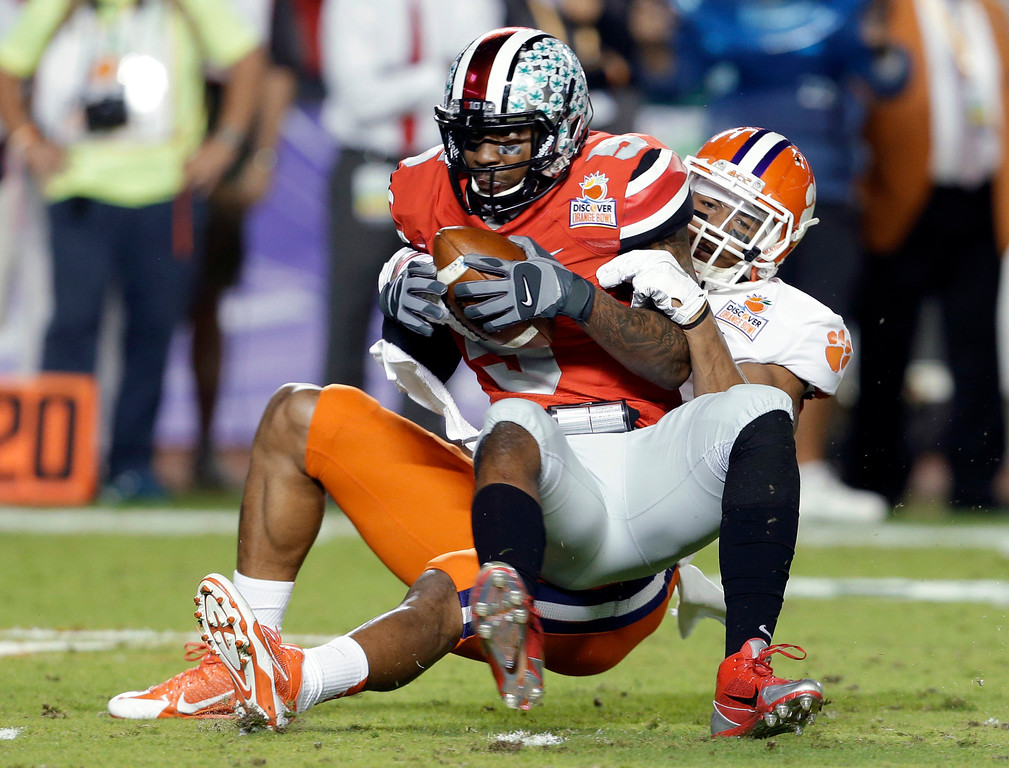 . Ohio State quarterback Braxton Miller is brought down by Clemson defensive end Vic Beasley during the first half of the Orange Bowl NCAA college football game, Friday, Jan. 3, 2014, in Miami Gardens, Fla. (AP Photo/Lynne Sladky)