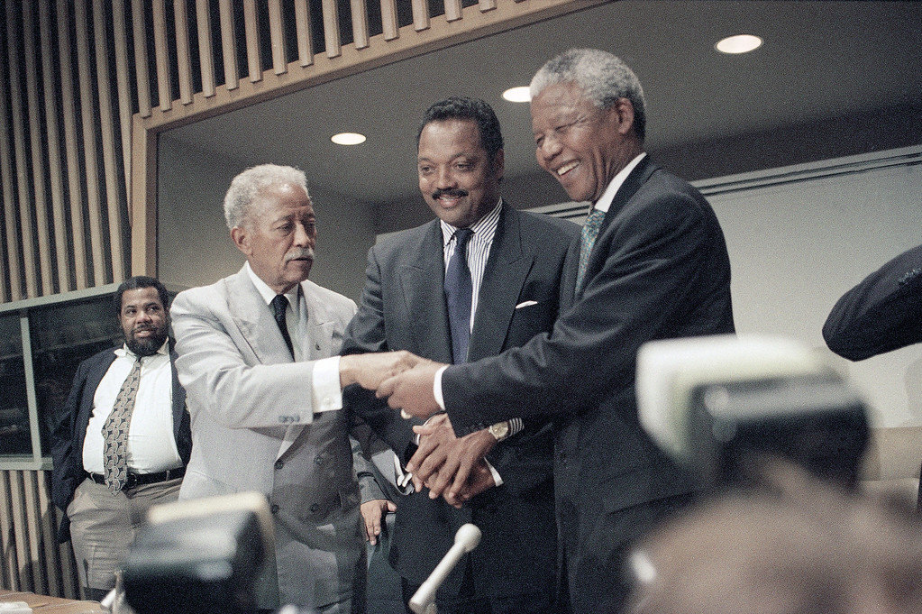 . New York City Mayor David Dinkins, left, and the Rev. Jesse Jackson, center, joins hands with African National Congress President Nelson Mandela Friday, Sept. 24, 1993 in New York, following a press conference at the United Nations. Mandela, in addition to calling for a lifting of sanctions against South Africa, also confirmed Friday that the ANC has been holding secret talks with right-wing Afrikaaners about the establishment of a semi-autonomous white homeland. (AP Photo/Bebeto Matthews)
