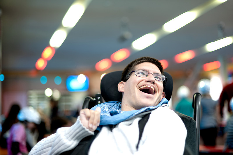 Twenty-Six Year old Man Smiling.  Photographed in an indoor setting (the cafe of an ice skating rink) while seated in his wheelchair