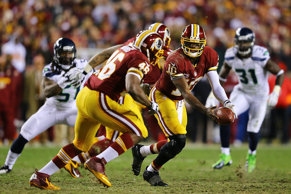 . Robert Griffin III #10 laterals to Alfred Morris #46 of the Washington Redskins in the third quarter against the Seattle Seahawks during the NFC Wild Card Playoff Game at FedExField on January 6, 2013 in Landover, Maryland.  (Photo by Al Bello/Getty Images)