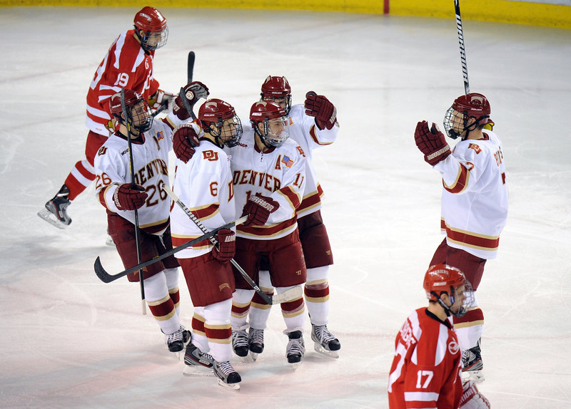 . University of Denver\'s Chris Knowlton (11) and teammates celebrate Knowlton\'s goal in the 3rd period of the game at Magness Arena in Denver, Colo. on Saturday, December 29, 2012. Hyoung Chang, The Denver Post