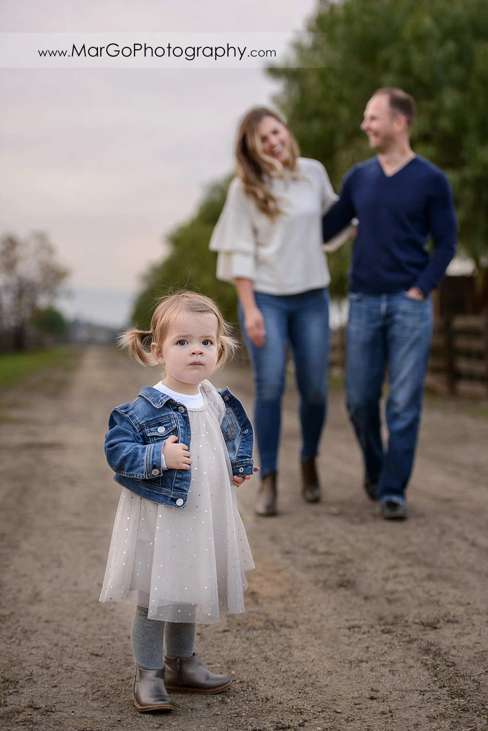 little girl in white dress and jeans jacket standing in front of mother in white sweater and jeans and father wearing navy blue sweater during family session at San Jose Martial Cottle Park