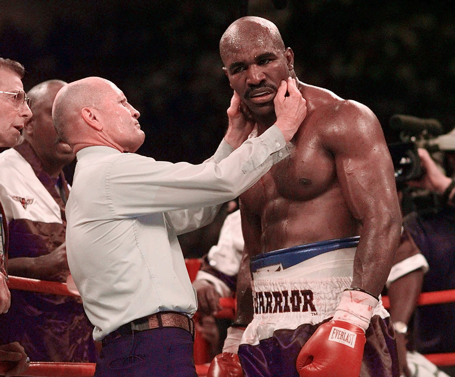 . Evander Holyfield has his ear checked by referee MIlls Lane after he was bit in the ear by Mike Tyson in the third round of their WBA Heavyweight match Saturday, June 28, 1997, at the MGM Grand in Las Vegas.  (AP Photo/Mark J. Terrill)