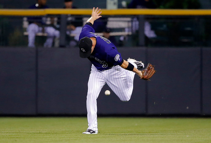 . Colorado Rockies right fielder Michael Cuddyer misses a fly ball hit by Los Angeles Dodgers\' Dee Gordon during the fifth inning of a baseball game Monday, Sept. 15, 2014, in Denver. (AP Photo/Jack Dempsey)