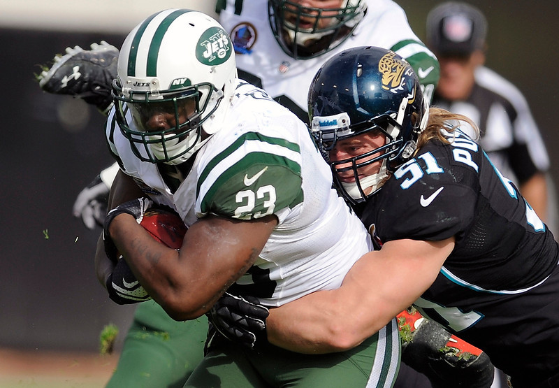 . New York Jets running back Shonn Greene (23) is tackled by Jacksonville Jaguars middle linebacker Paul Posluszny (51) after a short gain during the first half of an NFL football game, Sunday, Dec. 9, 2012, in Jacksonville, Fla. (AP Photo/Stephen Morton)