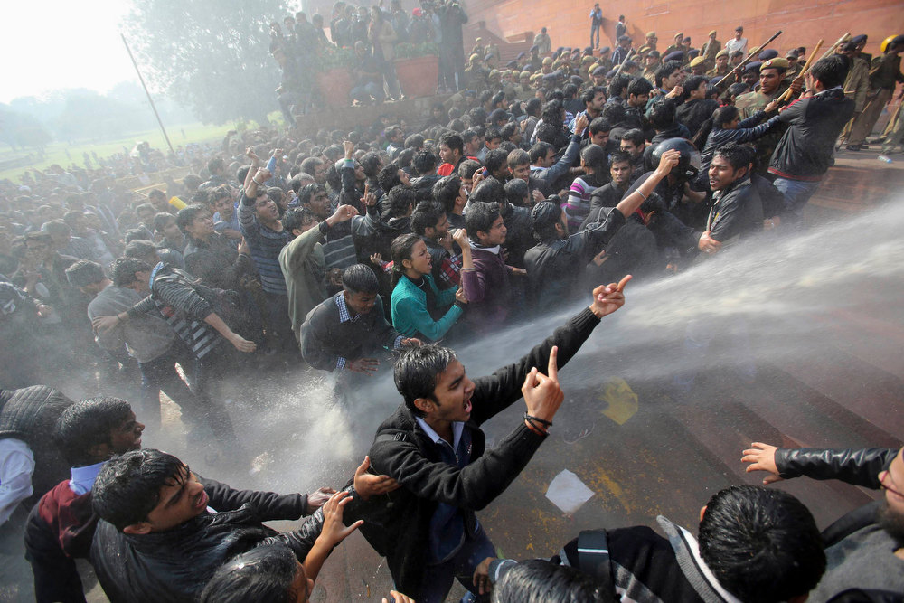Description of . Demonstrators shout slogans as police use water cannons to disperse them near the presidential palace during a protest rally in New Delhi December 22, 2012. Indian police used batons, tear gas and water cannon to turn back thousands of people marching on the presidential palace on Saturday in intensifying protests against the gang-rape of a woman on the streets and on social media. REUTERS/Adnan Abidi