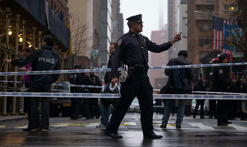. A police officer gestures to pedestrians to use the other side of the street at the site of a shooting near Columbus Circle in Manhattan, New York December 10, 2012. New York City police are looking for a suspect after a person was shot in the head in Manhattan, local media reported.  REUTERS/Adrees Latif