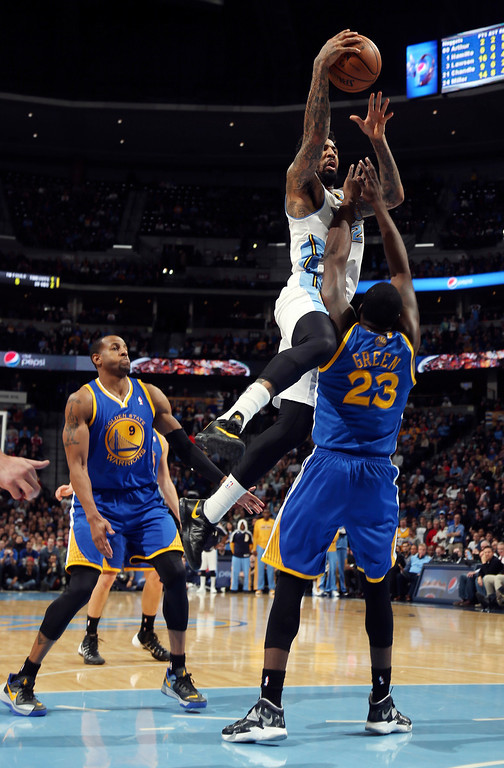 . Denver Nuggets forward Wilson Chandler, back right, drives for a shot and is called for charging into Golden State Warriors forward Draymond Green, front right, as Warriors guard Andre Iguodala stands near in the fourth quarter of the Warriors\' 89-81 victory in an NBA basketball game in Denver on Monday, Dec. 23, 2013. (AP Photo/David Zalubowski)
