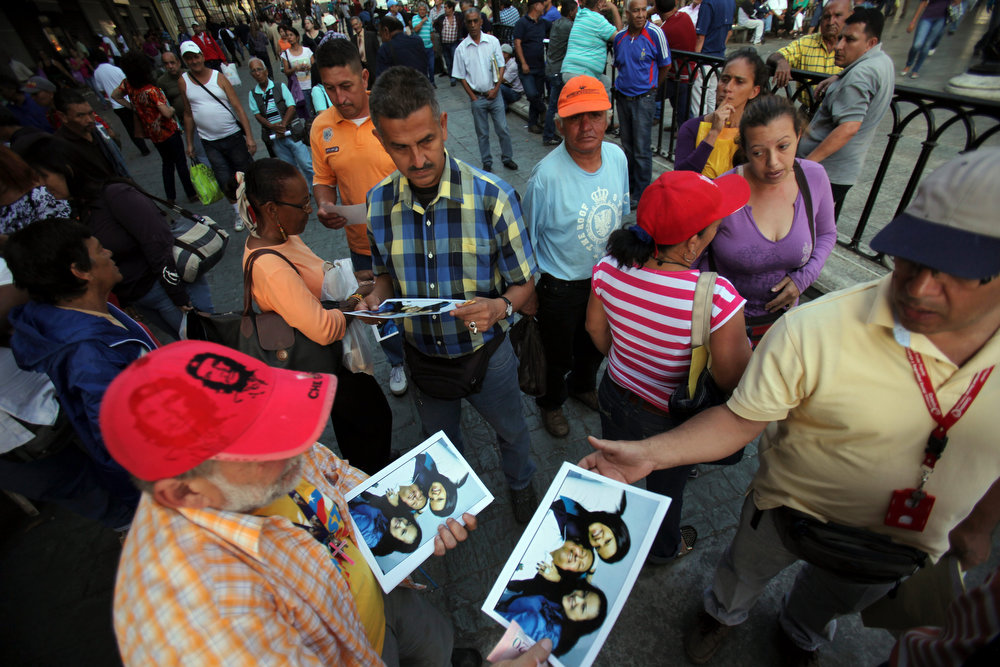 Description of . A man sells prints at 20 bolivars each, about 3.00 U.S. dollars, of one of the photographs released Friday by the Venezuelan government showing President Hugo Chavez with his daughters Maria Gabriela, left, and Rosa Virginia, right, at Bolivar square in Caracas, Venezuela, Friday, Feb. 15, 2013. Amid widespread speculation and rumors in Venezuela about Chavez's delicate condition following his Dec. 11 cancer surgery, the government released the first photos of the ailing president in more than two months on Friday, presenting images of him smiling alongside his daughters in Cuba. (AP Photo/Fernando Llano)