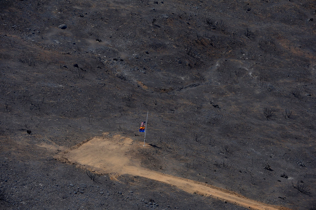 . Flags fly Sunday, July 7, 2013, near the site where 19 firefighters died battling a wildfire in Yarnell, Ariz, The elite crew of firefighters were overtaken by the out-of-control blaze as they tried to protect themselves from the flames under fire-resistant shields last Sunday. (AP Photo/Mark J. Terrill)