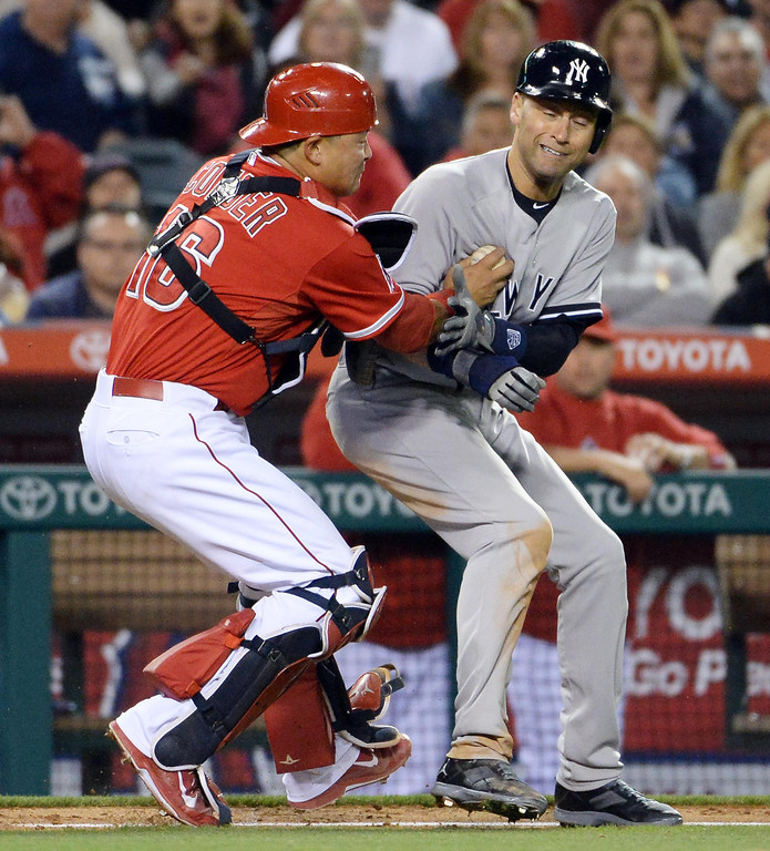 . Los Angeles Angels catcher Hank Conger (16) tags out New York Yankees\' Derek Jeter (2) in a run down between third and home plate in the eighth inning of a baseball game at Anaheim Stadium in Anaheim, Calif., on Tuesday, May 6, 2014.  (Keith Birmingham Pasadena Star-News)