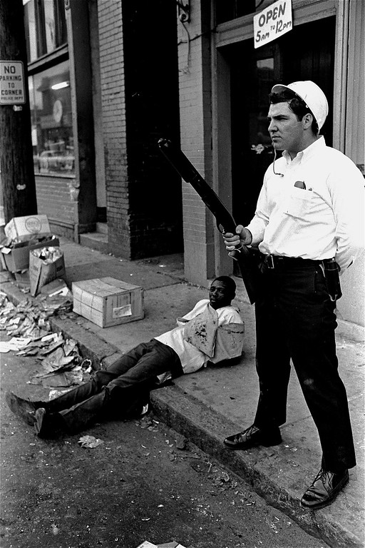 . Helmeted Memphis policeman stands guard with a shotgun over a suspect who the policeman said had been captured while attempting to loot a store in downtown Memphis, March 28, 1968.  City and state police, along with some 4,000 National Guardsmen fanned out through the city to enforce a 7 p.m. curfew.  (AP Photo/Jack Thornell)