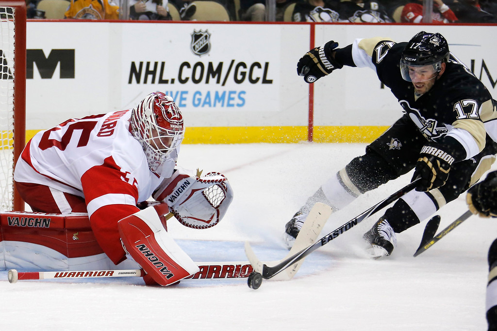 . Detroit Red Wings goalie Jimmy Howard (35) stops a shot by Pittsburgh Penguins\' Blake Comeau (17) during the second period of a NHL pre-season hockey game in Pittsburgh Monday, Sept. 22, 2014. The Red Wings won 2-1. (AP Photo/Gene J. Puskar)