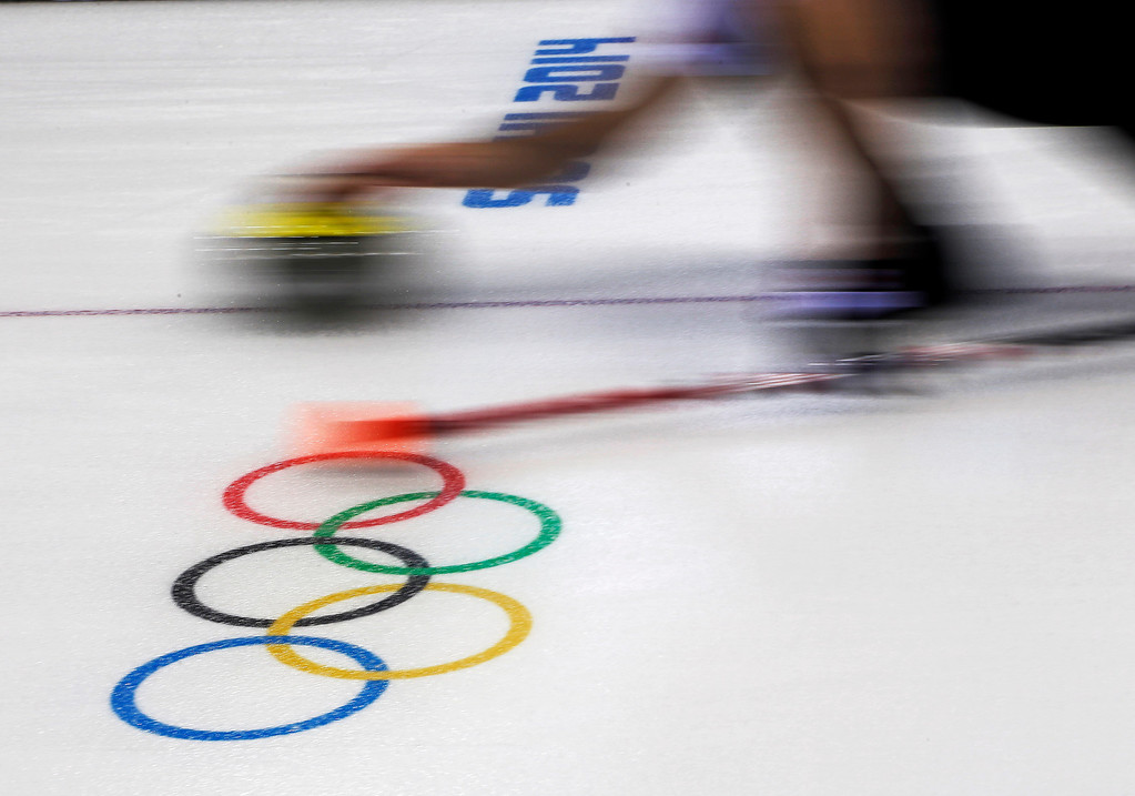. A men\'s curler delivers the stone during a round robin session at the 2014 Winter Olympics, Sunday, Feb. 16, 2014, in Sochi, Russia. (AP Photo/Morry Gash)