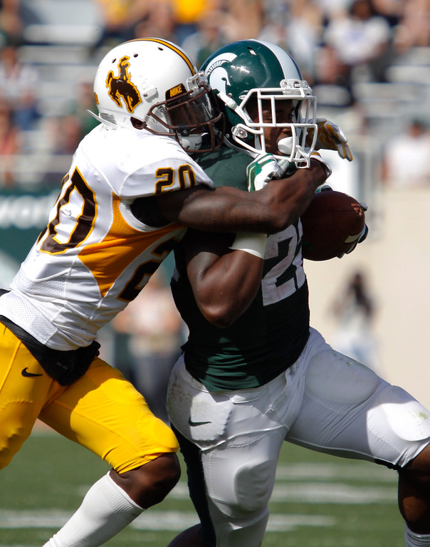 . Michigan State\'s Delton Williams, right, is tackled by Wyoming\'s Blair Burns during the fourth quarter of an NCAA college football game, Saturday, Sept. 27, 2014, in East Lansing, Mich. Michigan State won 56-14. (AP Photo/Al Goldis)
