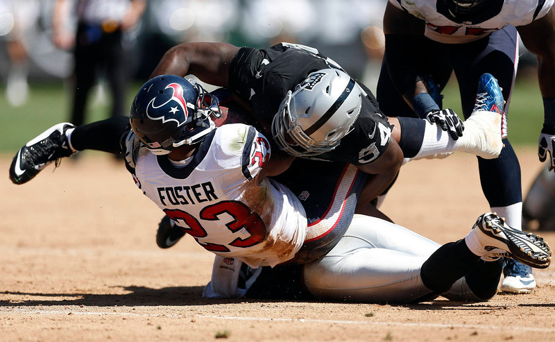 . Houston Texans running back Arian Foster (23) is brought down with the ball by Oakland Raiders defensive tackle Antonio Smith in the second quarter of an NFL football game Sunday, Sept. 14, 2014, in Oakland, Calif. (AP Photo/Beck Diefenbach)