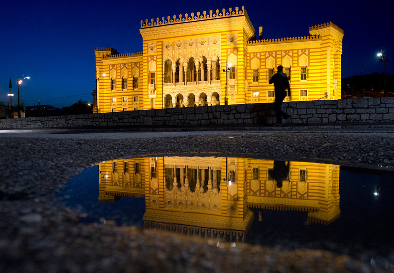 . In this Tuesday, April 22, 2014, the City Hall is reflected in a puddle in Sarajevo, Bosnia-Herzegovina. The city will host a number events around the Centenary of World War I, including a conference of historians and a concert. (AP Photo/Amel Emric)